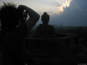 A tourist photographing Buddha against the afternoon sky (Borobudur, Java)